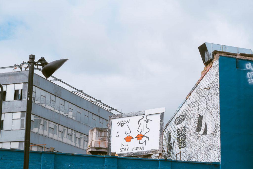"""Plakatwand """"Stay Human"""" zwischen zwei Gebäuden."""